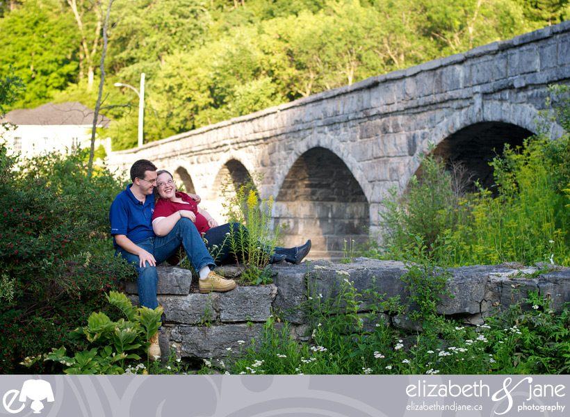 Engagement Photo: Couple in love sitting on a rock wall by the 5-Span bridge in Pakenham, Ontario
