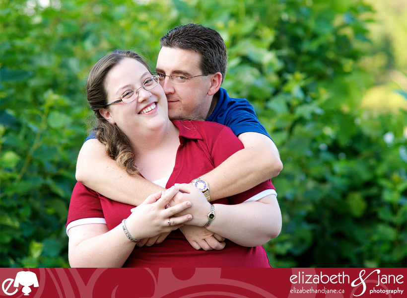 Engagement Photo: couple standing embracing in greenery