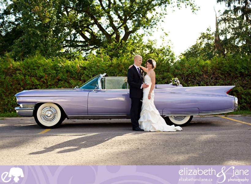 Wedding Photo: bride and groom standing by a vintage purple car