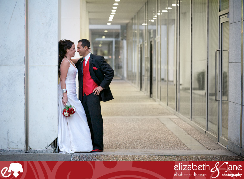 Wedding Photo: bride and groom leaning against a grey wall looking at each other