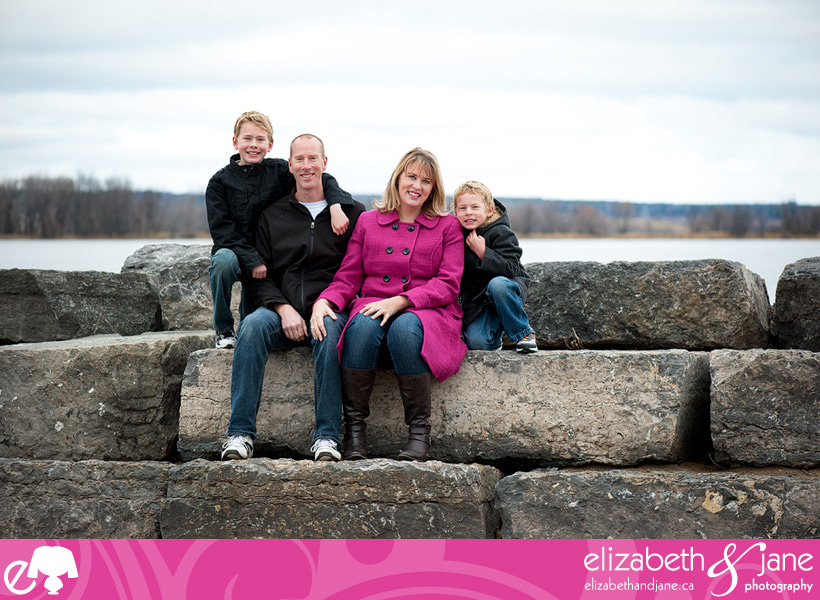 Family sitting on rocks by a lake