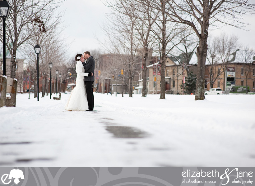 Wedding Photo: bride and groom kissing along a snowy path