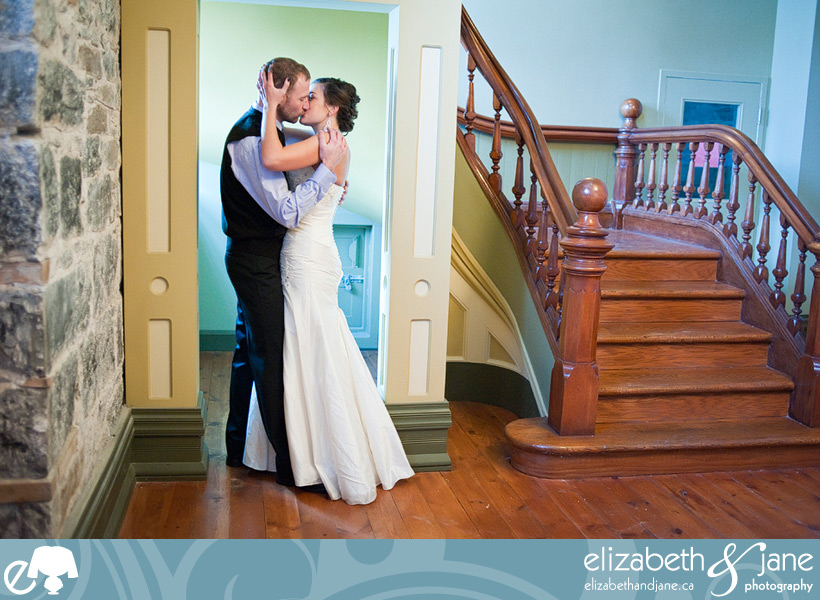Wedding Photo: bride and groom kissing in a doorway