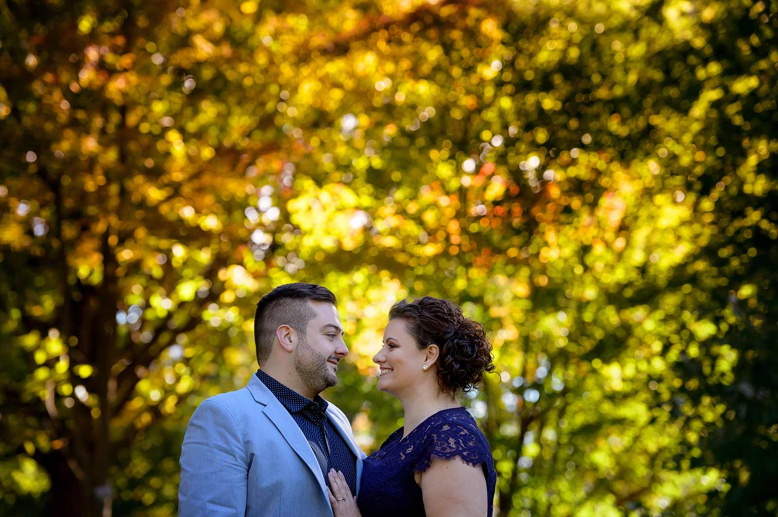 Carina and Alex's Engagement session in Ottawa at the Arboretum Central Experimental Farm with the couple cuddling together amongst the fall trees
