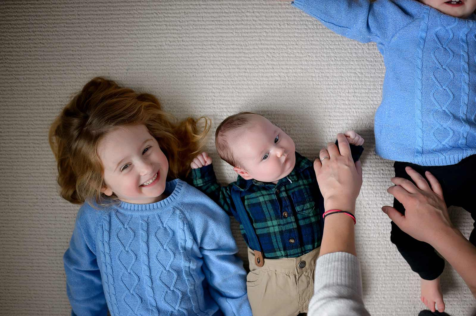 Baby Connor with his sisters when one sister is escaping the frame of the photo in Ottawa, Ontario