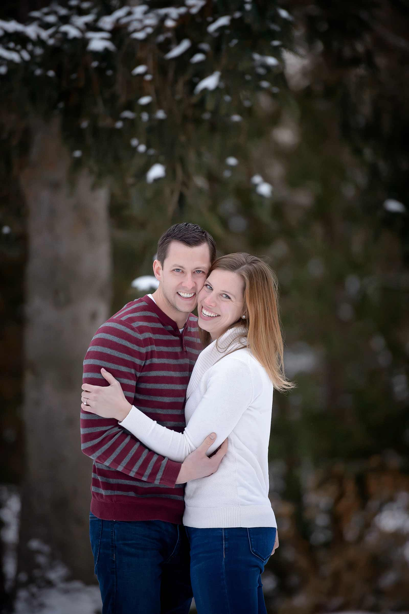 Bridget and Mike's winter engagement session in Manotick, Ottawa, Ontario, cuddling together outside in the snow