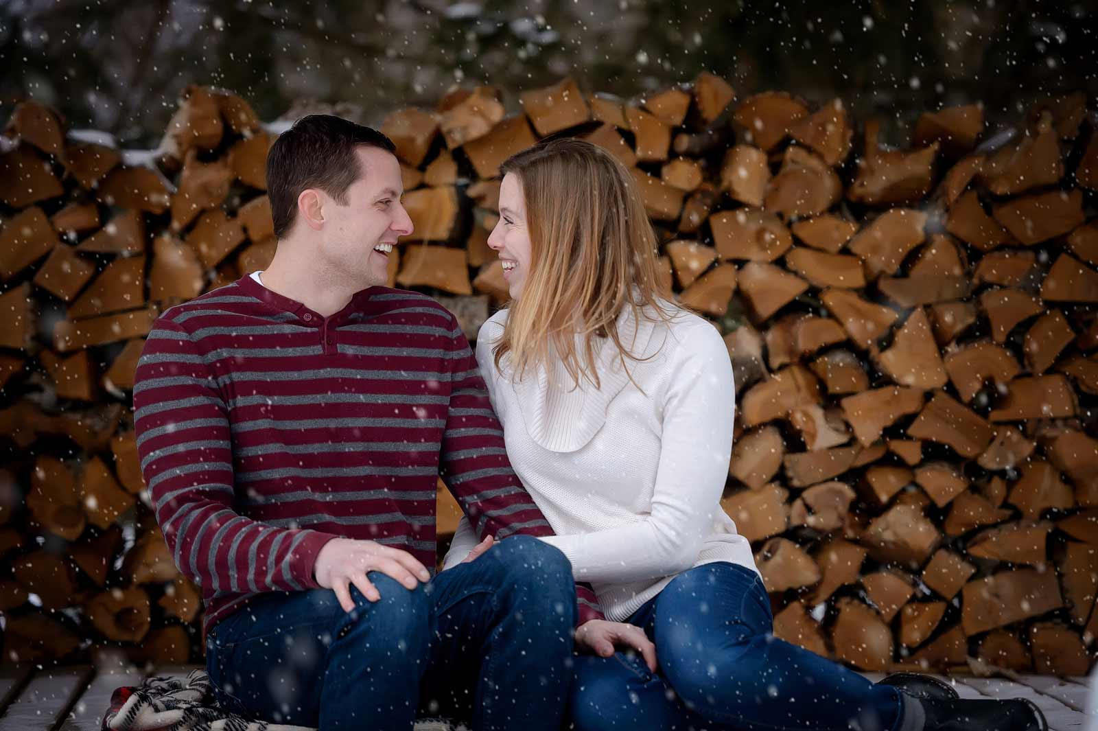Bridget and Mike's winter engagement session in Manotick, Ottawa, Ontario, cuddling in the snow in front of a wood pile while snowing