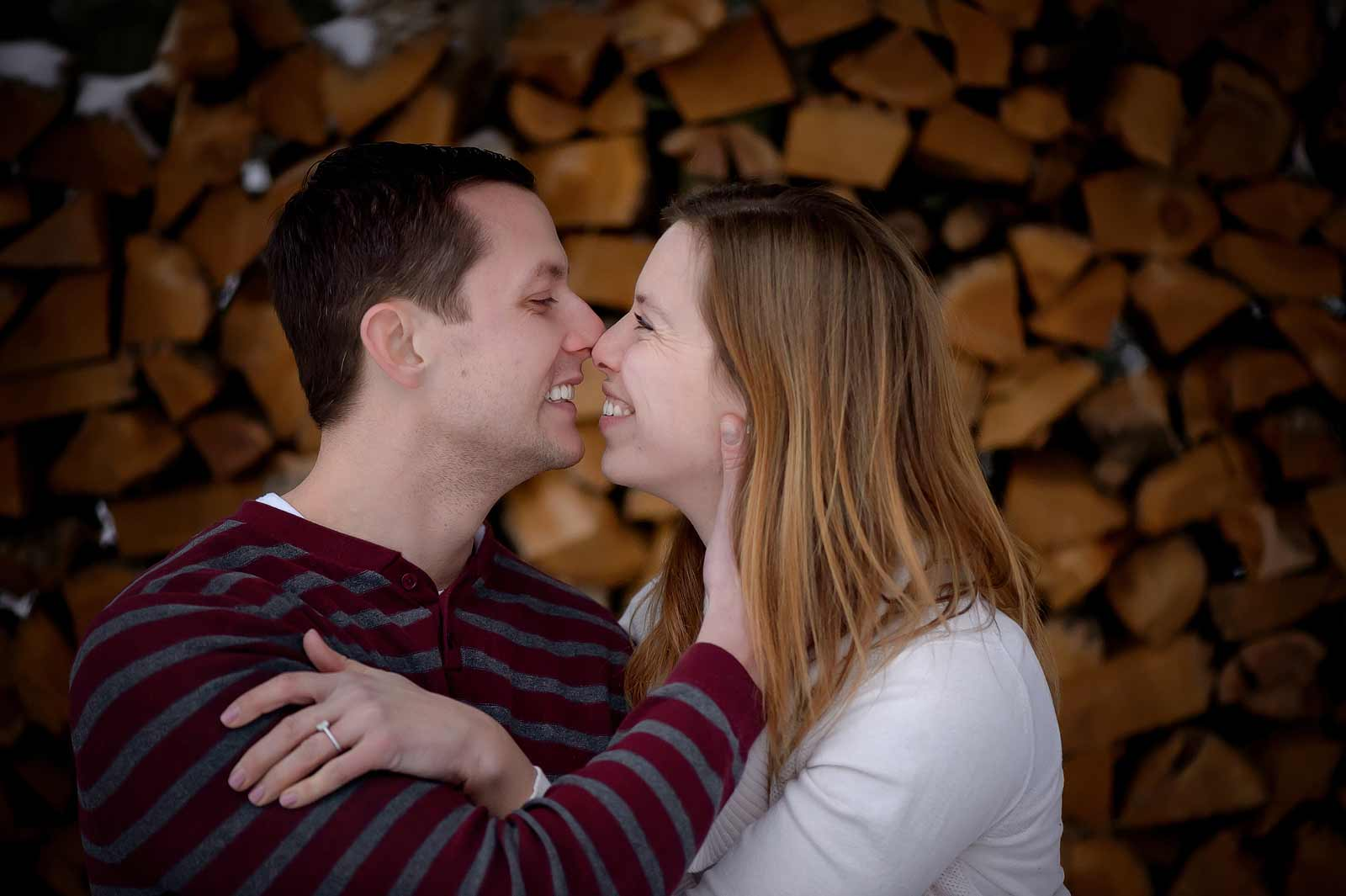 Bridget and Mike's winter engagement session in Manotick, Ottawa, Ontario, cuddling in the snow in front of a wood pile