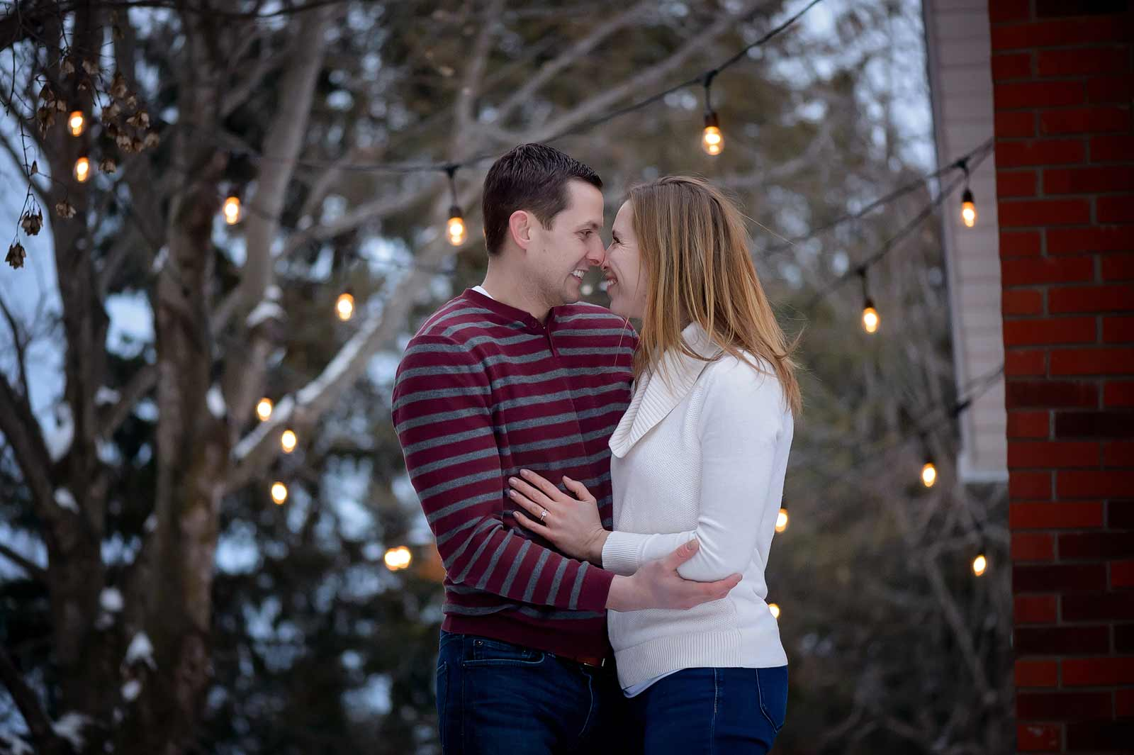 Bridget and Mike's winter engagement session in Manotick, Ottawa, Ontario, in the snow looking at each other with love in front of Edison lights