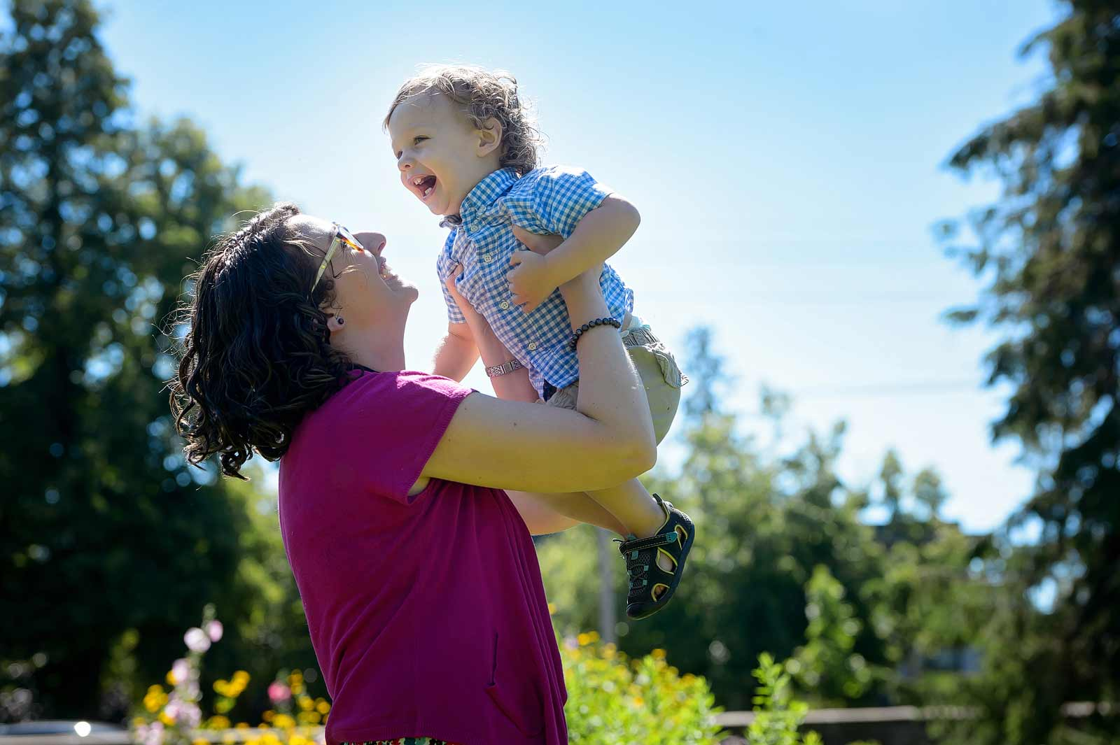 Mom throwing her young toddler son in the air for laughs at Maplelawn gardens in the summer