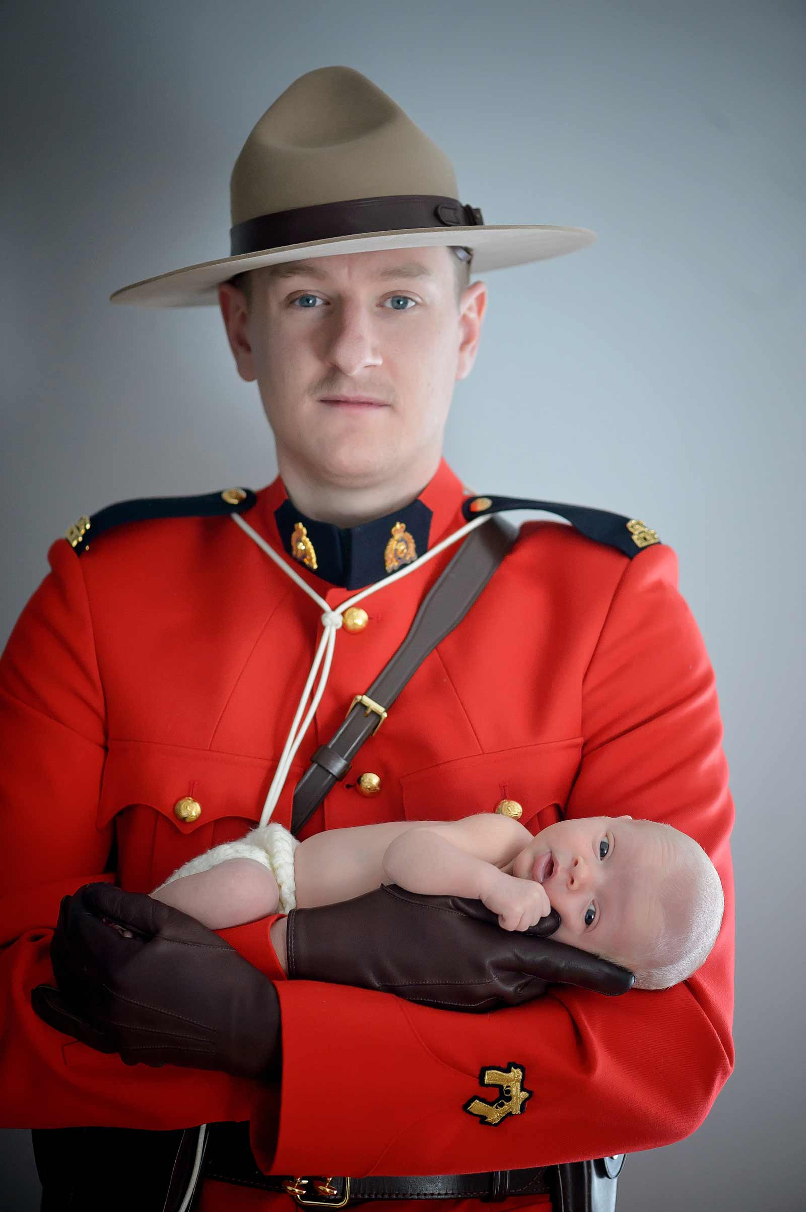 RCMP Father holding his newborn son in uniform