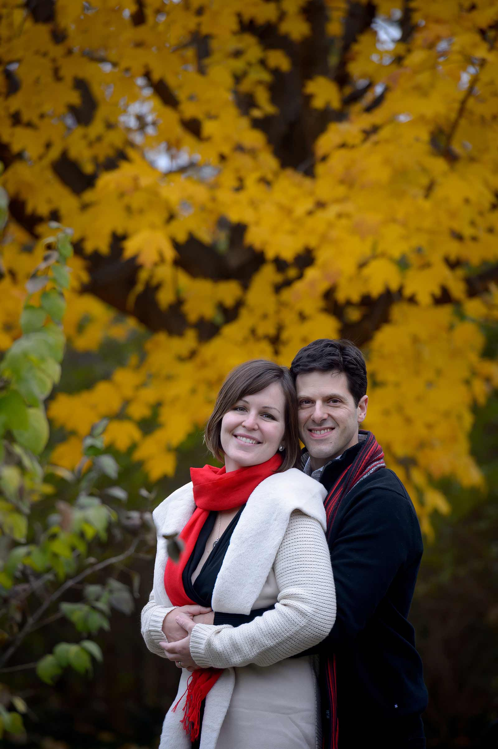 Portrait of a couple smiling at the camera with the fall leaves behind them at Maplelawn Gardens