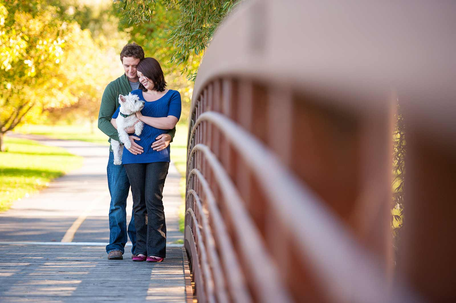 Family standing with their West Highland Terrier dog on a bridge at the Arboretum