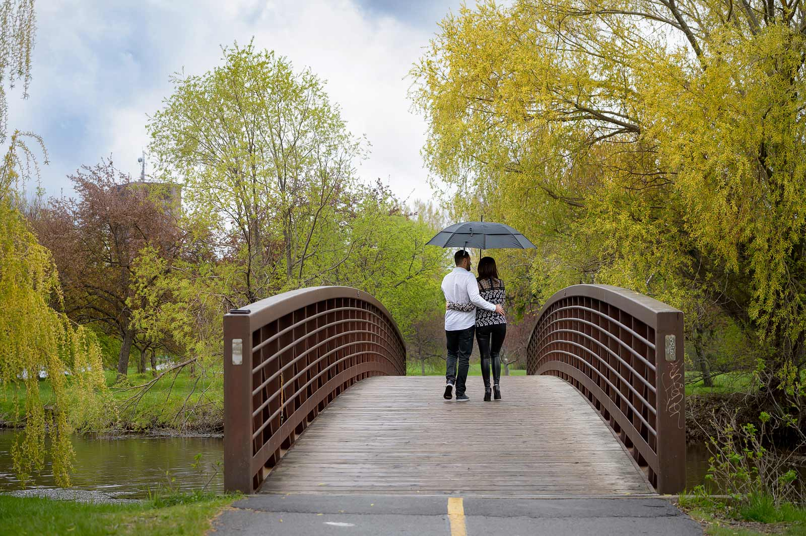 Couple walking on a bridge in the rain with an umbrella at the Arboretum
