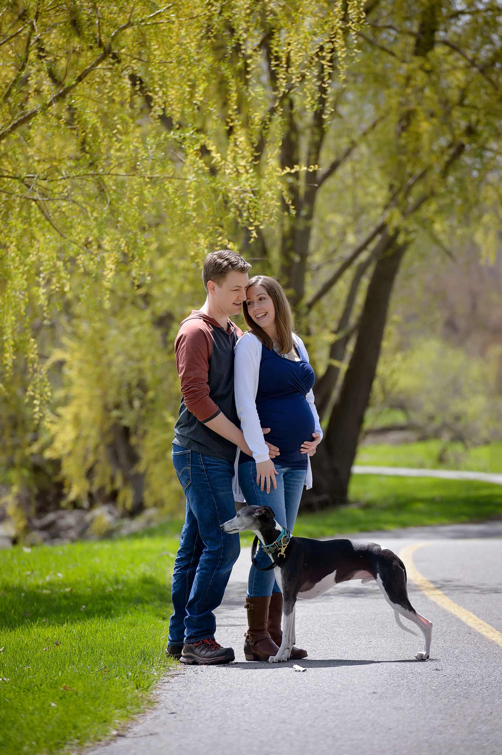 Maternity session with a dog standing on a pathway in Ottawa at the Arboretum