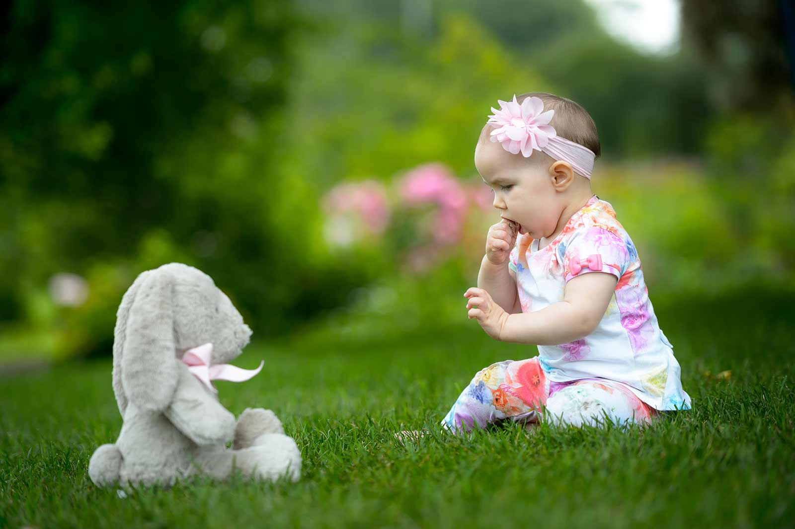 Baby sharing a snack with her bunny on the grass at the Ornamental Gardens in Ottawa