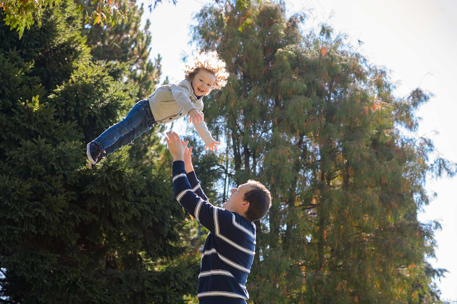 Kid laughing flying through the air into Dad's arms at the Ornamental Gardens