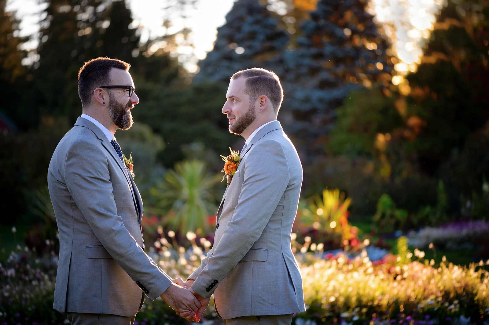 Same sex gay wedding husbands holding hands having a romantic moment in the fall at the Ornamental Gardens in Ottawa