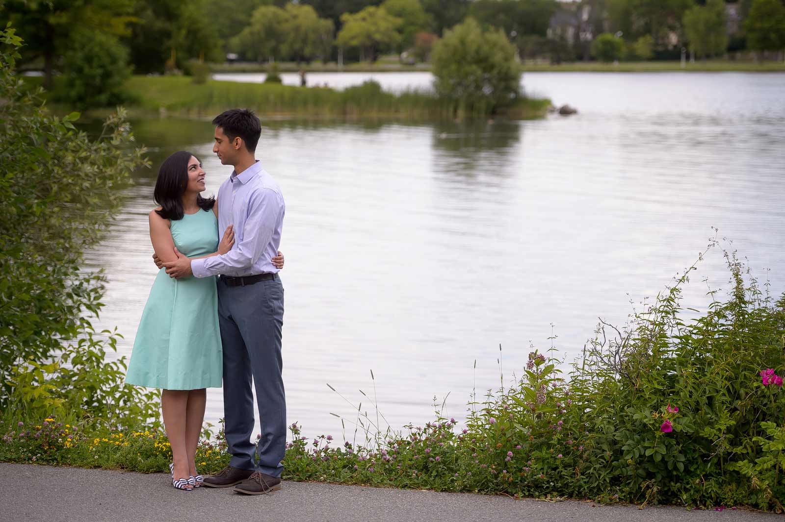A couple standing by the water at Dow's Lake for their engagement session