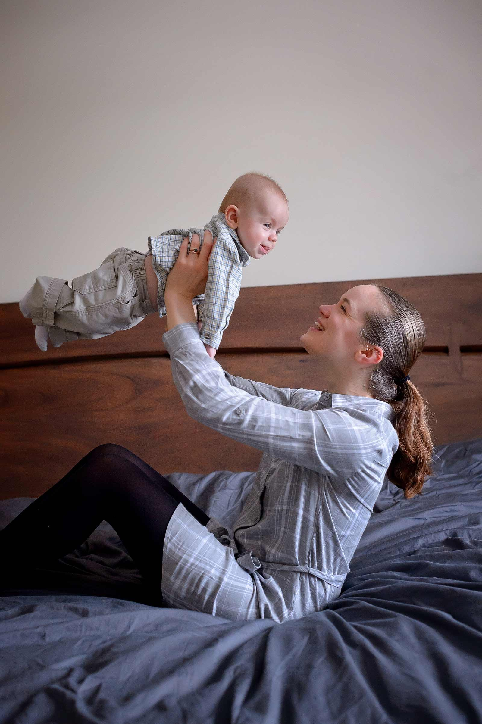 Mom flying baby boy over her head while he smiles