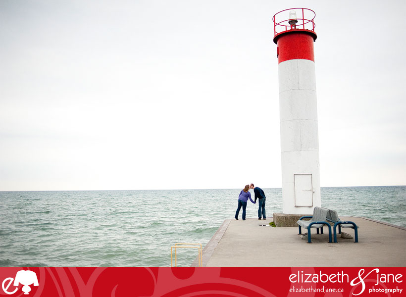Engagement photo: couple kissing by a lighthouse
