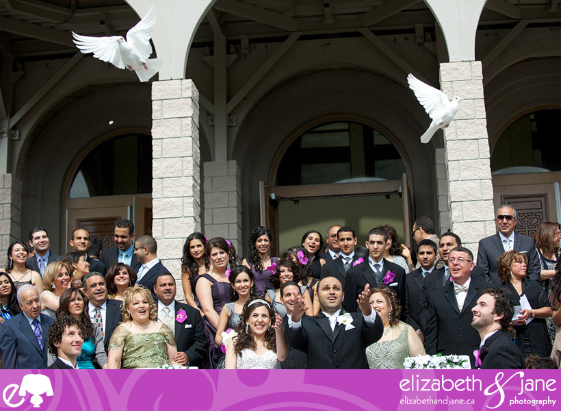 Bride and groom with wedding guests letting doves go