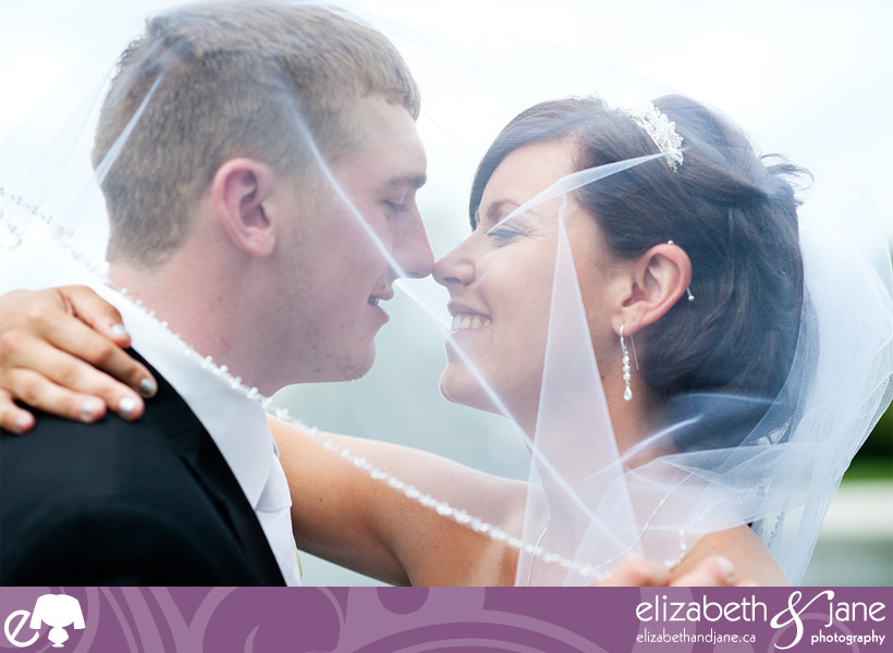 Bride and groom touching noses under her veil