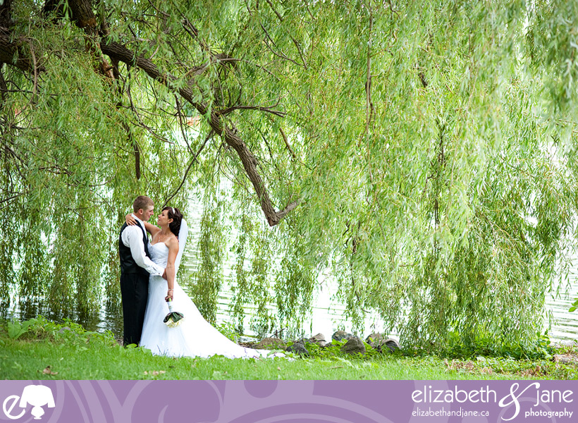 Bride and Groom standing under a willow tree