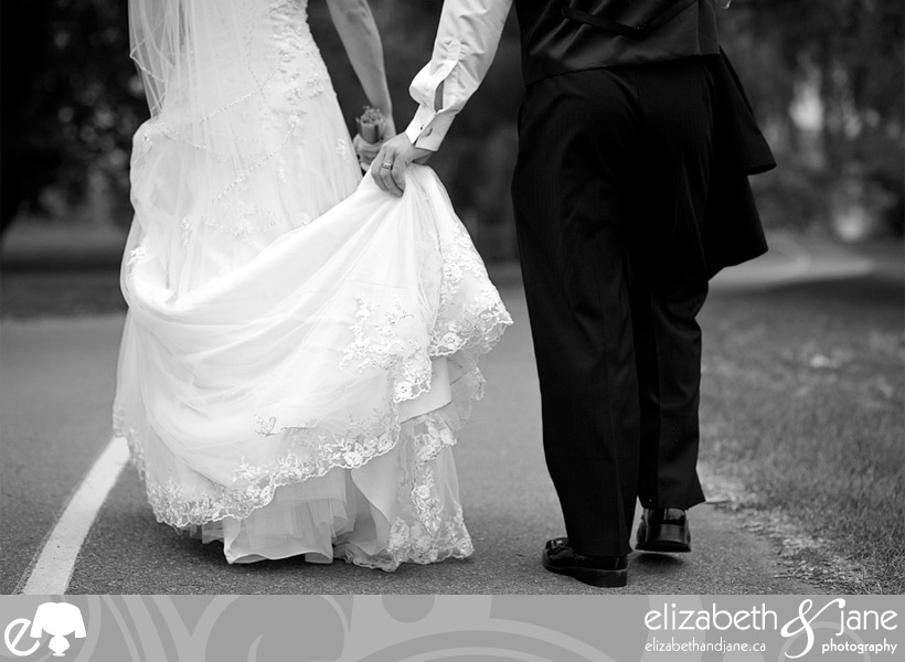 Bride and groom walking away in black and white
